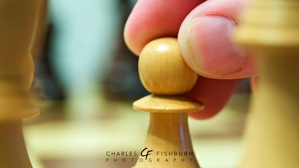 Close-up of a hand moving a white pawn